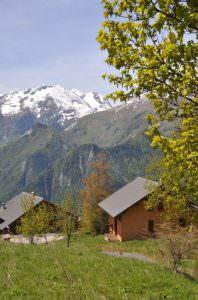 Chalet Rouge ou Blanc in het zomerse groen van Villard Reculas tegen de achtergrond van Rochetaillee